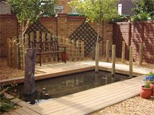 Wooden decked pond surround designed and installed by cambridge fencing and decking.