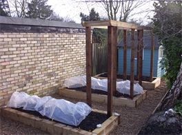 Wooden sleeper raised vegetable beds and arches designed and installed by cambridge fencing and decking.