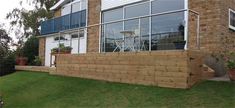 Contemporary modern decking with wooden steps and stainless steel hand rail designed and installed by cambridge fencing and decking.
